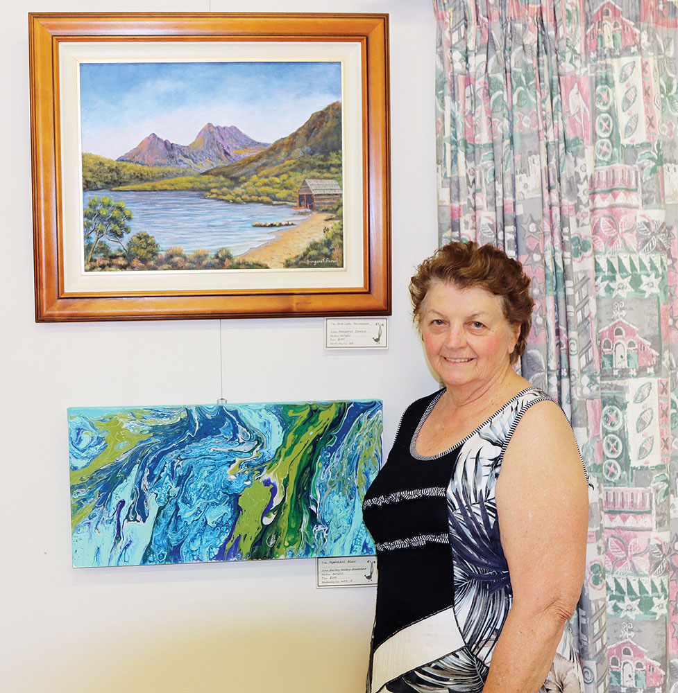 Margaret Dennis with her paintings