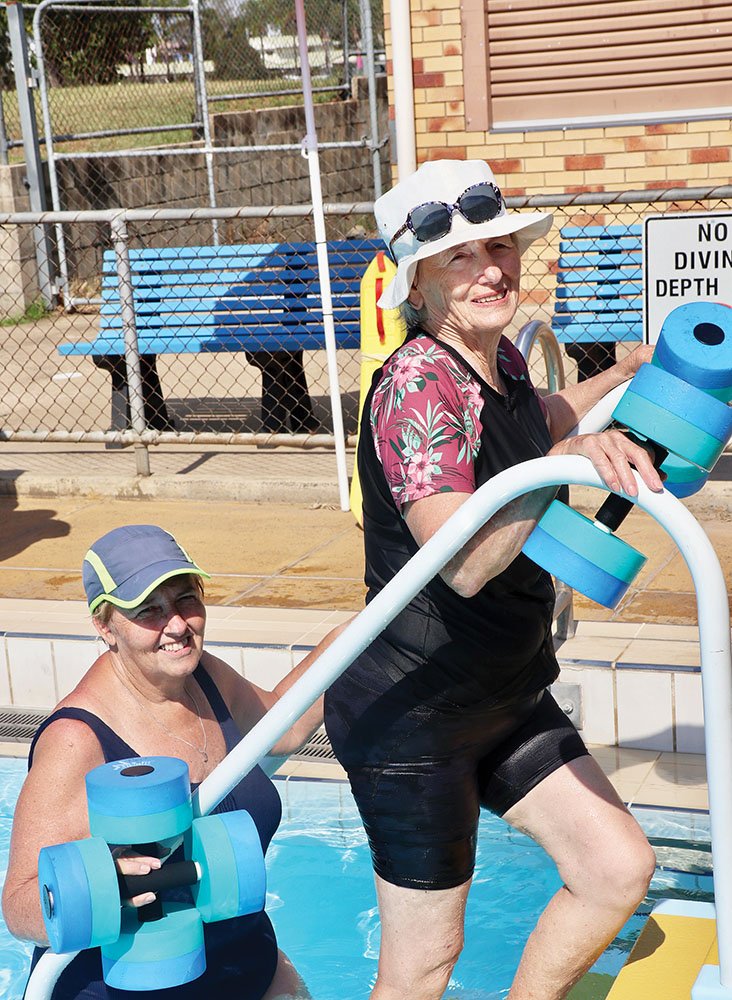 Two women emerging from pool after lesson