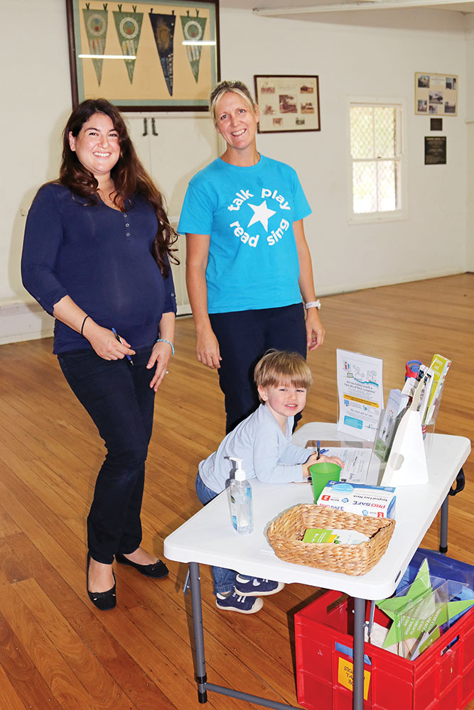 Mum Tal and Heidi from First Five Forever watch as Gabriel  'signs into' the First Five Forever Rhymetime session